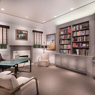 Foto på ett stort vintage arbetsrum, med vita väggar, heltäckningsmatta, en öppen vedspis, en spiselkrans i sten, ett fristående skrivbord och grått golv