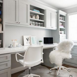 Imagen de sala de manualidades tradicional renovada, de tamaño medio, con paredes grises, suelo de madera en tonos medios, escritorio empotrado y suelo marrón