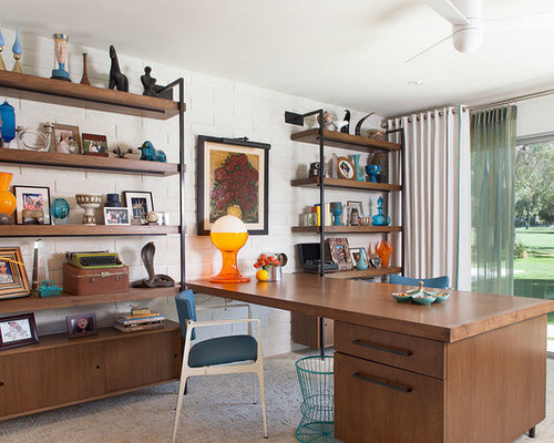mid sized 1950s study room idea in los angeles with white walls carpet and
