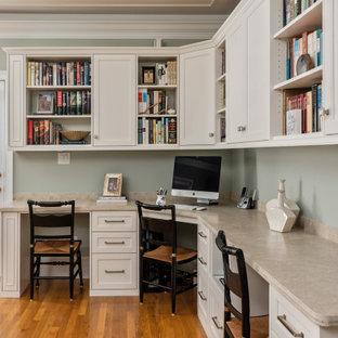 Idéer för ett litet klassiskt hemmabibliotek, med gröna väggar, ljust trägolv, ett inbyggt skrivbord och brunt golv