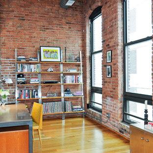 Foto de despacho urbano, sin chimenea, con paredes rojas, suelo de madera en tonos medios y escritorio independiente