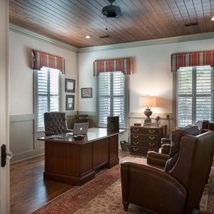 Idéer för ett stort klassiskt arbetsrum, med grå väggar, mellanmörkt trägolv, ett fristående skrivbord och brunt golv