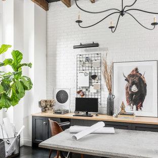 バンクーバーの広いトランジショナルスタイルのおしゃれな書斎 (白い壁、造り付け机、グレーの床、表し梁) の写真
