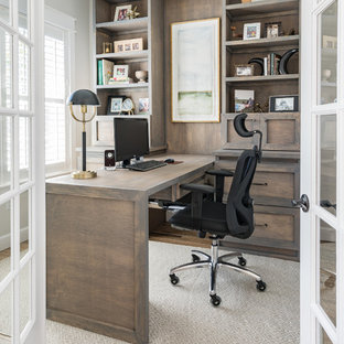 This is an example of a traditional home office and library in Tampa with white walls, light hardwood flooring, a built-in desk and brown floors.