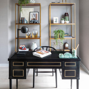 Contemporary study in London with grey walls, a freestanding desk and grey floors.