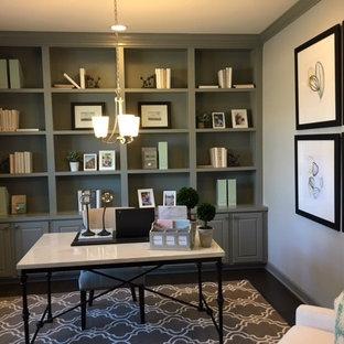 Modelo de despacho minimalista, de tamaño medio, con paredes verdes, suelo de madera oscura, escritorio empotrado y suelo marrón