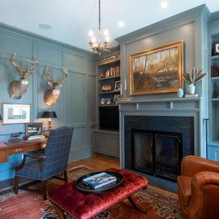 他の地域の広いカントリー風おしゃれな書斎 (青い壁、無垢フローリング、標準型暖炉、石材の暖炉まわり、自立型机、茶色い床) の写真