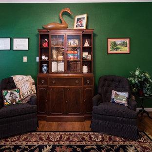 Foto di un grande studio classico con pareti verdi, pavimento in legno massello medio e scrivania autoportante