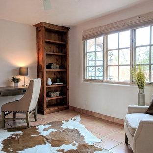 Идея дизайна: маленькое рабочее место в стиле фьюжн с белыми стенами, полом из терракотовой плитки, отдельно стоящим рабочим столом и оранжевым полом без камина
