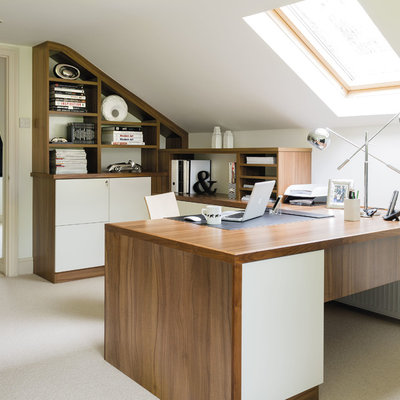 Inspiration for a mid-sized contemporary built-in desk carpeted and beige floor study room remodel in Manchester with white walls