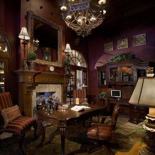 オーランドのトランジショナルスタイルのおしゃれなホームオフィス・仕事部屋 (赤い壁、ライムストーンの床、標準型暖炉、タイルの暖炉まわり、自立型机、ベージュの床) の写真