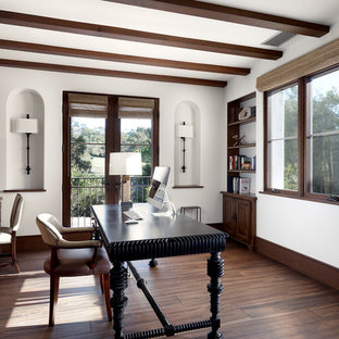Mediterranes Arbeitszimmer mit weißer Wandfarbe, dunklem Holzboden und freistehendem Schreibtisch in Los Angeles