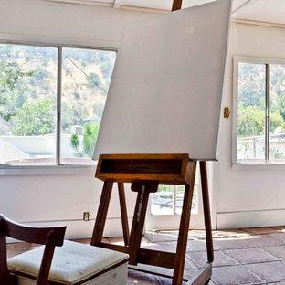 Modelo de estudio clásico renovado, pequeño, con paredes blancas, suelo de cemento y suelo rojo