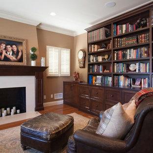 ロサンゼルスの中くらいの地中海スタイルのおしゃれなホームオフィス・書斎 (ライブラリー、茶色い壁、無垢フローリング、標準型暖炉、石材の暖炉まわり、茶色い床) の写真