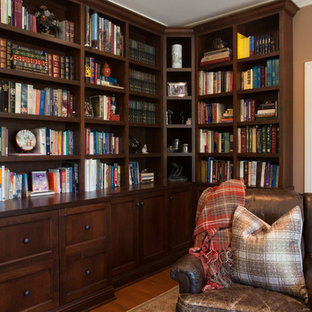 Example of a mid-sized tuscan medium tone wood floor and brown floor home office library design in Los Angeles with brown walls, a standard fireplace and a stone fireplace