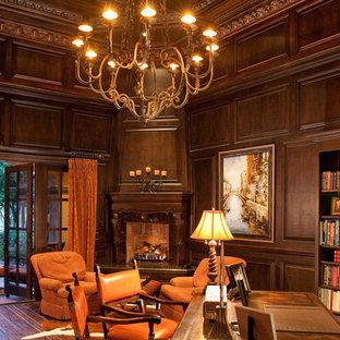 Immagine di un ampio studio in montagna con libreria, pareti marroni, parquet scuro, camino ad angolo, cornice del camino in legno, scrivania autoportante e pavimento marrone