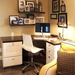 Foto på ett litet funkis hemmabibliotek, med beige väggar, klinkergolv i porslin och ett fristående skrivbord