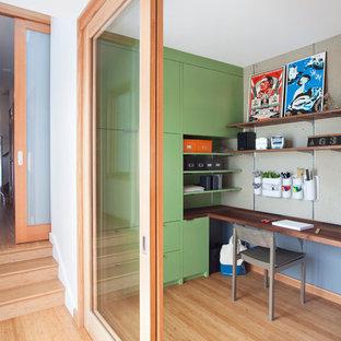 Idéer för ett litet modernt arbetsrum, med gröna väggar, mellanmörkt trägolv och ett inbyggt skrivbord