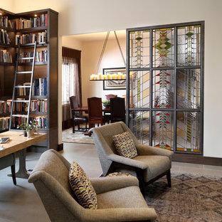 Modern inredning av ett mellanstort arbetsrum, med ett bibliotek, vita väggar, klinkergolv i keramik, en dubbelsidig öppen spis, en spiselkrans i metall, ett fristående skrivbord och grått golv