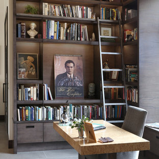 This is an example of a medium sized contemporary home office and library in Boise with ceramic flooring, a freestanding desk, grey floors, a reading nook, white walls, a two-sided fireplace and a metal fireplace surround.