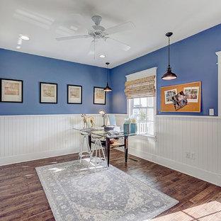 Ejemplo de sala de manualidades boiserie, de estilo americano, grande, con paredes azules, suelo de madera en tonos medios, escritorio independiente, suelo marrón y boiserie
