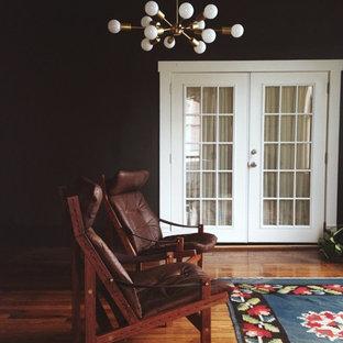 Esempio di un ufficio stile americano di medie dimensioni con pareti nere e pavimento in legno massello medio