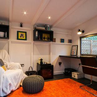 Idee per un piccolo atelier design con pareti bianche, scrivania incassata e pavimento nero