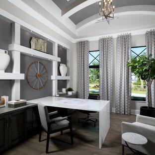 Mediterranes Arbeitszimmer ohne Kamin mit Arbeitsplatz, grauer Wandfarbe, dunklem Holzboden, Einbau-Schreibtisch und braunem Boden in Sonstige