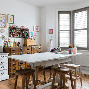 Design ideas for a rural craft room in London with white walls, medium hardwood flooring, a freestanding desk and brown floors.