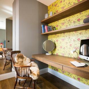 Inredning av ett klassiskt hemmabibliotek, med flerfärgade väggar, mellanmörkt trägolv och ett inbyggt skrivbord