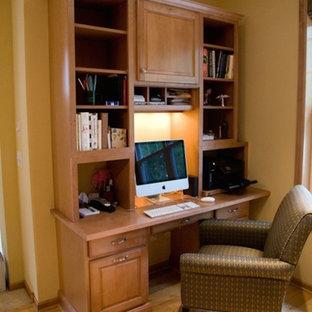 Foto de despacho pequeño, sin chimenea, con paredes amarillas, suelo de madera clara y escritorio empotrado