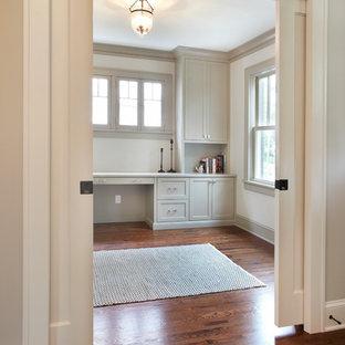 Modelo de despacho tradicional renovado, de tamaño medio, con paredes grises, suelo de madera en tonos medios y escritorio independiente