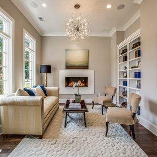 Inspiration för stora klassiska hemmabibliotek, med grå väggar, mörkt trägolv, ett fristående skrivbord, brunt golv, en standard öppen spis och en spiselkrans i trä
