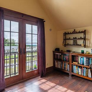 シアトルのヴィクトリアン調のおしゃれなホームオフィス・書斎 (ライブラリー、黄色い壁、ラミネートの床、茶色い床) の写真