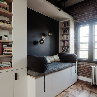 Mid-sized danish medium tone wood floor home office library photo in New York with blue walls