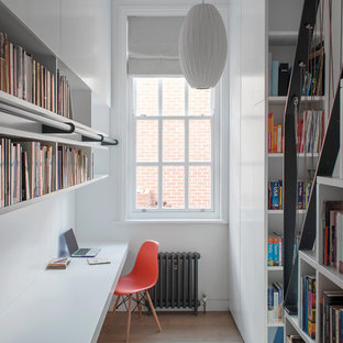 Design ideas for a contemporary home office and library in London with a reading nook, white walls, medium hardwood flooring, a built-in desk and brown floors.