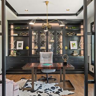 Landhaus Arbeitszimmer mit Arbeitsplatz, beiger Wandfarbe, braunem Holzboden, freistehendem Schreibtisch und braunem Boden in Cincinnati