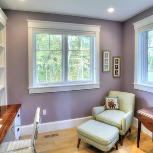 Large beach style home office and library in Bridgeport with purple walls, light hardwood flooring and a built-in desk.