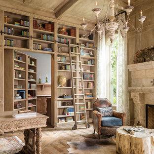 Modelo de despacho mediterráneo con paredes beige, suelo de madera en tonos medios, chimenea tradicional, marco de chimenea de piedra y escritorio independiente