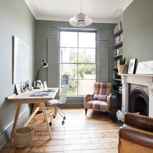 Photo of a traditional study in London with green walls, medium hardwood flooring, a freestanding desk, brown floors and a standard fireplace.