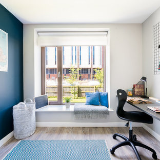 Inspiration for a contemporary home office and library in Other with blue walls, a built-in desk and brown floors.