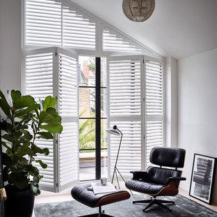 Idee per uno studio minimal di medie dimensioni con libreria, pareti bianche, parquet chiaro e pavimento beige
