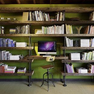 Modern inredning av ett stort hemmastudio, med gröna väggar, heltäckningsmatta och ett inbyggt skrivbord