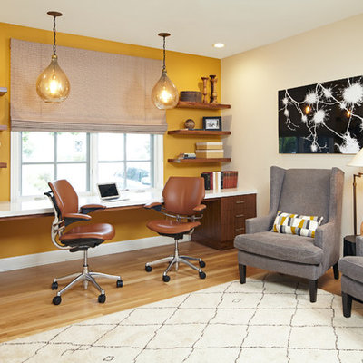 Large transitional built-in desk light wood floor study room photo in Los Angeles with yellow walls and no fireplace