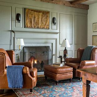 Cette image montre un grand bureau rustique avec un mur gris, un sol en bois brun, une cheminée standard, un manteau de cheminée en pierre et un bureau indépendant.