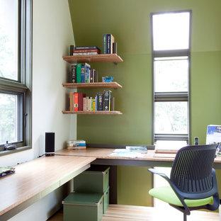 ナッシュビルのモダンスタイルのおしゃれなホームオフィス・書斎 (緑の壁、無垢フローリング、造り付け机、ベージュの床) の写真