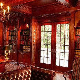 Неиссякаемый источник вдохновения для домашнего уюта: большой кабинет в викторианском стиле с коричневыми стенами, темным паркетным полом, встроенным рабочим столом и коричневым полом без камина