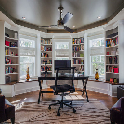 Example of a classic freestanding desk dark wood floor study room design in Chicago with white walls