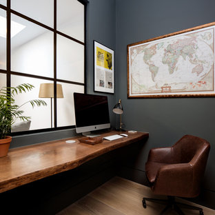 Small contemporary study in London with black walls, light hardwood flooring and a built-in desk.