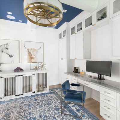 Example of a large transitional built-in desk light wood floor and coffered ceiling study room design in Austin with white walls
